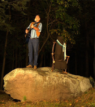 Photo of Johnny Jules with guitar on a rock singing at the moon